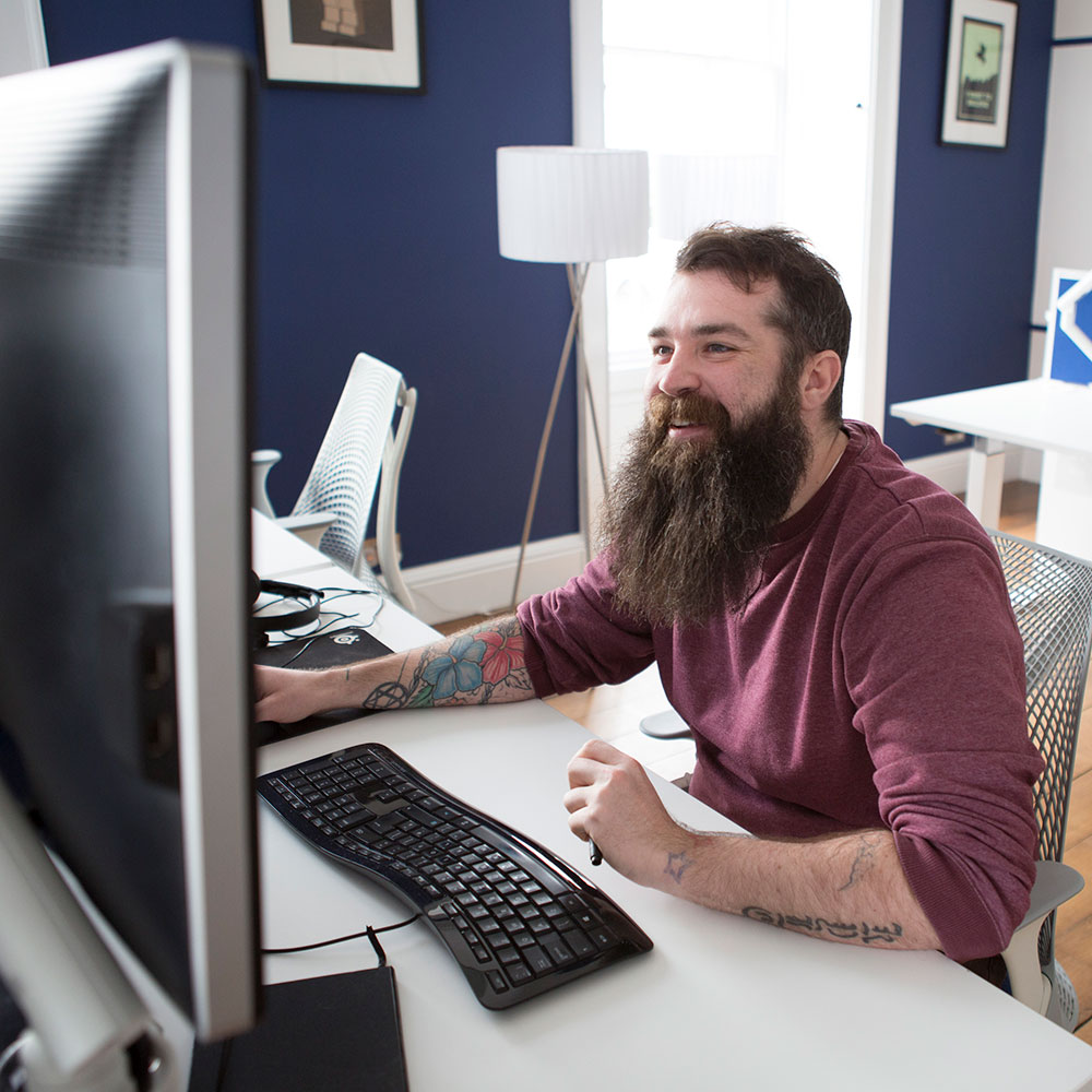 A smiling man with a beard working at an ergonomic desk.